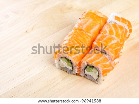 Sushi roll Philadelphia on wooden board, closeup