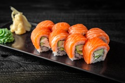 Sushi roll (Philadelphia) with salmon, smoked eel, avocado, cream cheese on black background. Sushi menu. Japanese food.