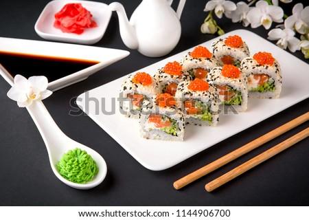 Sushi roll sushi  with fresh juicy salmon, Philadelphia cheese, sesame, red caviar salmon roe, avocado. Sushi menu. Japanese food. Asian food