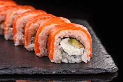 Sushi roll with salmon, avocado and cheese laid out on a black plate. Sushi menu. Japanese food.