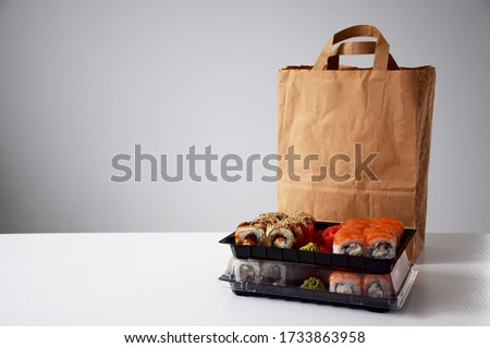 Sushi rolls in plastic box near paper package on white table. Delivery. Take away