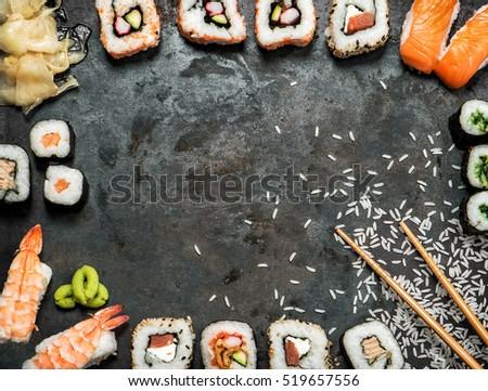 Sushi rolls, maki, nigiri, salmon, wasabi, shrimp, tuna, tofu, rice, avocado, pickled ginger. Japanese food background. Vintage toned picture