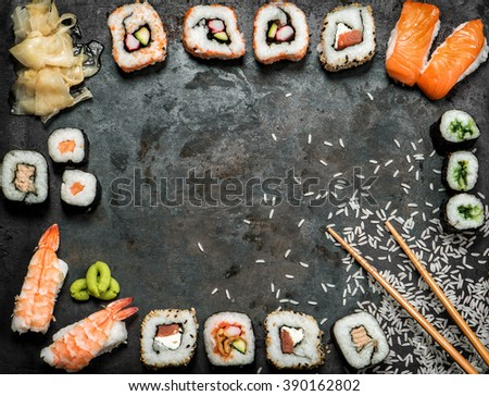 Sushi rolls, maki, nigiri, salmon, wasabi, shrimp, tuna, tofu, rice, avocado, pickled ginger. Asian food background. Dark toned picture