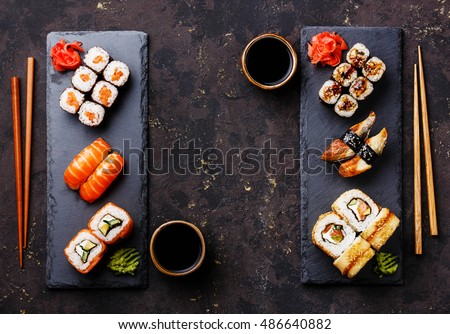 Sushi rolls, maki, nigiri Set served for two on black stone slate on dark background copy space