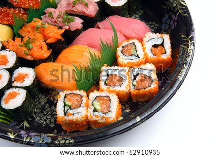 Sushi rolls on a black plate.