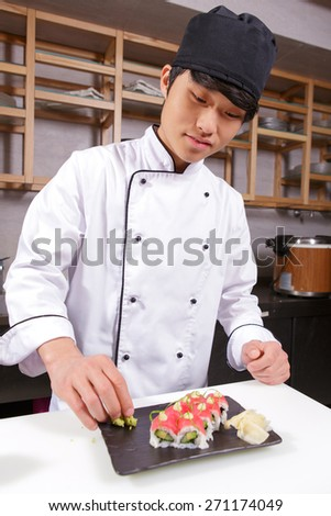 Sushi rolls presentation. Young Japanese cook putting wasabi on a rectangular plate with tuna sushi rolls