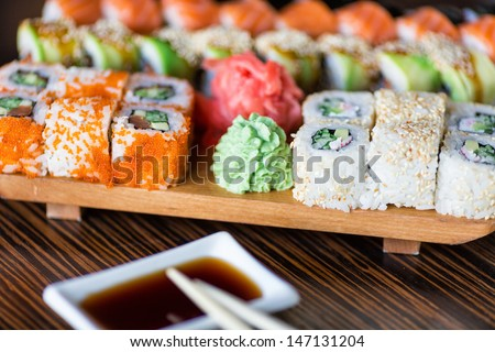 Sushi rolls served on a wooden plate in a restaurant