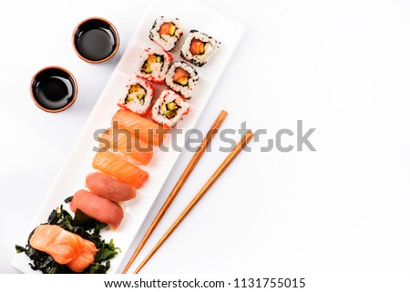 Sushi rolls set with salmon and tuna fish isolated on white background from above. Top view of traditional japanese cuisine. Asian food with chopsticks design.