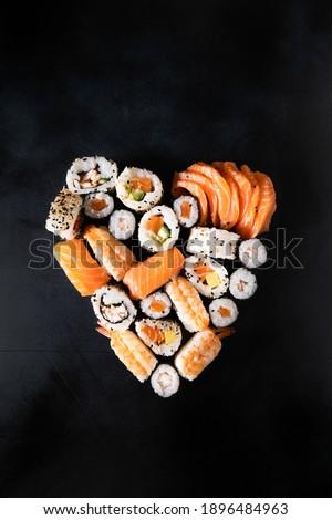 Sushi rolls unagi nigiri uramaki serving in the form of heart on a dark background. valentine's day romantic dinner. banner food delivery sushi rolls japanese cuisine