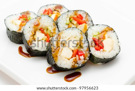 sushi rolls with salmon and vegetables on a square plate
