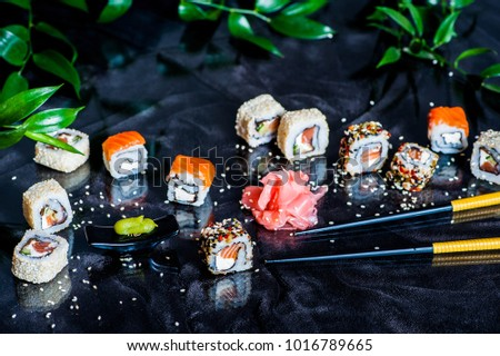 Sushi salmon and sushi spice maki with black glass table in background