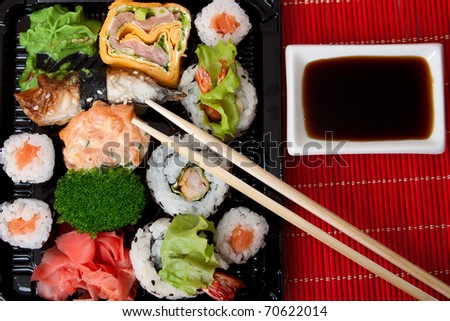 Sushi, sauce and chopstick on a red bamboo napkin. Series japanese food - stock photo