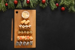 Sushi set as Christmas tree served on wooden chopping board as Xmas decoration on black background. View from above. Space for text. Flat lay style.