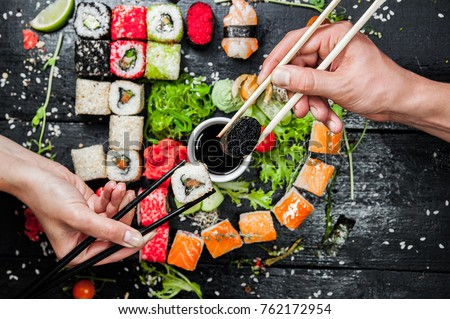 Sushi set in hand with chopsticks for sushi