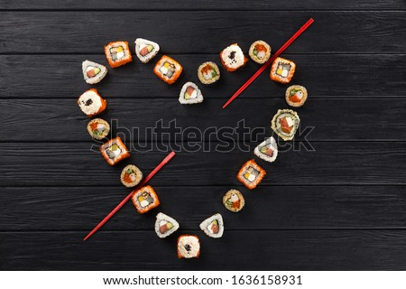 Sushi set in the shape of a heart. Valentine's Day. maki, gunkan and sushi rolls served on stone slate. Sushi set on a stone plate and dark concrete background. Sushi roll set and chopsticks.