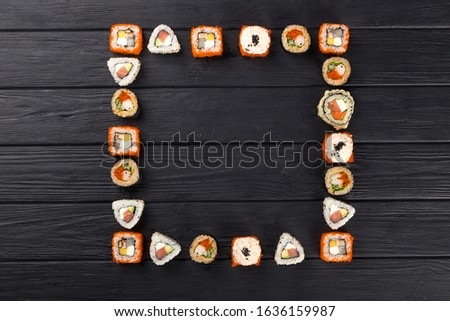 Sushi set in the square. Valentine's Day. maki, gunkan and sushi rolls served on stone slate. Sushi set on a stone plate and dark concrete background. Sushi roll set and chopsticks. Fresh Japanese cui