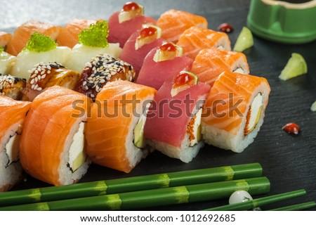 Sushi Set nigiri and sushi rolls on gray stone slate on metal background