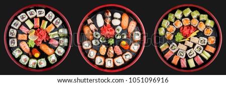 Sushi Set nigiri, rolls and sashimi served in traditional Japan black Sushioke round plate. On dark background