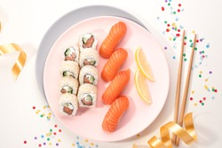 Sushi set on a pink plate on bright background. Philadelphia maki roll and salmon sashimi nigiri. Festive mood. Christmas and New Year party. Table covered in confetti, streamers and ribbons. Close up
