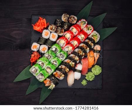 Sushi set: Ronin Roll, California Maki, Salmon Maki, Fudziyama Maki, Avocado Maki, Salmon Nigiri, Tuna Nigiri, Octopus , Shrimp Nigiri, Seabass Nigiri  placed on a black textured background