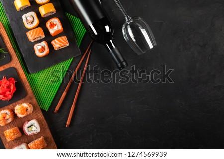 Sushi Set sashimi and sushi rolls, bottle of wine and a glass served on stone slate.