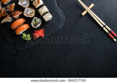 Sushi set with wasabi and ginger on black stone tray on black table. Top view.
