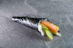 sushi temaki, hand roll with salmon: rice, nori seaweed, avocado, spicy sauce, cucumber, salmon on a stone background