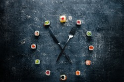 Sushi time in the form of a wall clock on a concrete background, sushi clock with fork and knife, concept of time to eat