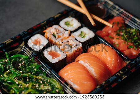 Sushi to go concept. Collection box with sushi. With sushi rolls and chopsticks. Maki. Sashimi. Salmon. Tuna. Wasabi. Asian. Japanese.