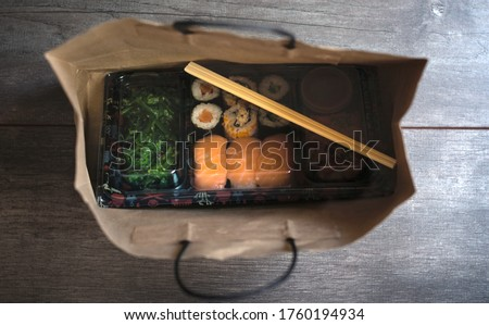 Sushi to go concept. Top view of takeaway box with sushi rolls and chopsticks in brown paper bag on wood floor. Maki. Sashimi. Salmon. Tuna. Wakame. Asian.Japanese. Paper bag.Take-away japanese food.