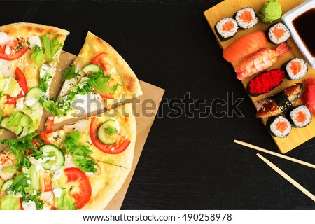 Sushi vs pizza. Business lunch concept, black stone background. Space for text