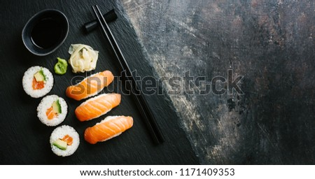 Sushi with avocado and salmon served on plate on dark table. Horizontal with copy space.