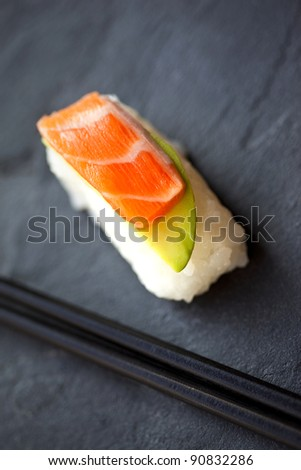 Sushi with salmon and avocado, pair of chopsticks