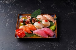 Sushi with salmon, eel, shrimp, tuna, scallop. On a plate on a black background. Decorated with bamboo leaf wasabi and ginger.