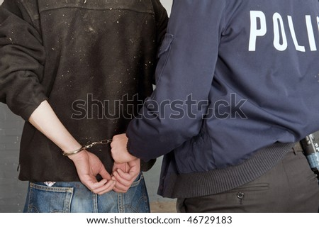Suspect being escorted away in handcuffs after a struggle - stock photo