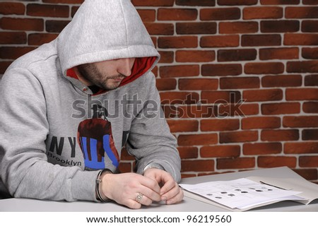 Suspect in handcuffs sitting at table against a break wall