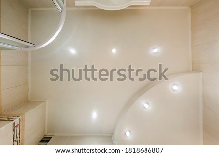 Photo of  suspended ceiling with halogen spots lamps and drywall construction in empty room in apartment or house. Stretch ceiling white and complex shape.