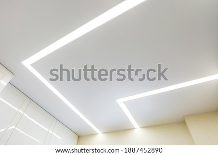 suspended ceiling with halogen spots lamps and drywall construction in empty room in apartment or house. Stretch ceiling white and complex shape. Сток-фото ©
