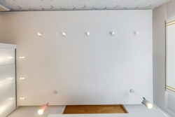 suspended ceiling with led diode spots lamps and drywall construction in empty room in apartment or house. Stretch ceiling white and complex shape.