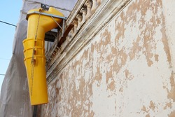 Suspended sections of the yellow garbage chute are attached to the facade of a historic building under construction. Yellow telescope debris chute.