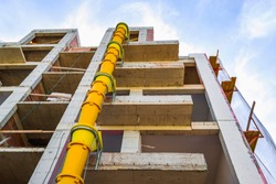 Suspended sections of yellow garbage chute on a facade of building under construction against blue sky with white cloud. Low angle view.