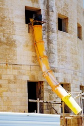 Suspended sections of yellow garbage chute on a facade of building under construction, Debris Chutes