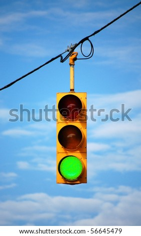 Suspended stoplight showing green, with sky background