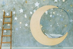 Suspended swing in the shape of the moon on a gray background with stars.