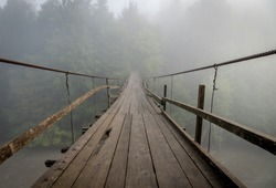 Suspended wooden bridge crossing the river to foggy mysterious forest