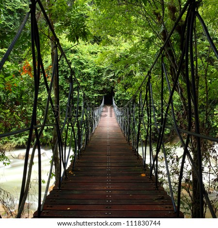 Suspension bridge across a stream in the jungle  at east, Thailand