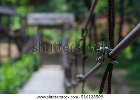 suspension bridge in the forest,Bridge with wires,Suspension bridge, Crossing the river, ferriage in the woods,Hanging bridge. Suspension bridge, bridge through the forest.canal across a river  #516128509
