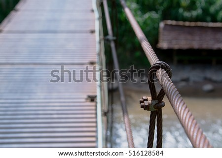 suspension bridge in the forest,Bridge with wires,Suspension bridge, Crossing the river, ferriage in the woods,Hanging bridge. Suspension bridge, bridge through the forest.canal across a river  #516128584