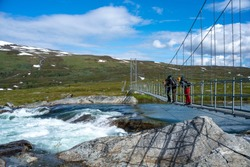 Suspension Bridge in the Mountains over fast flowing turbulent river in Padjelanta national park With Group of People or hikers on the bridge in Lapland, Sweden.