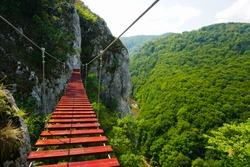 Suspension bridge made of wooden boards on via ferrata route Casa Zmeului, Padurea Craiului mountains, Romania